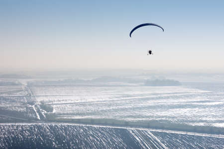 Aerial view of paramotor flying over the vastness of winter snowy French fields with horizon and blue sky Banque d'images