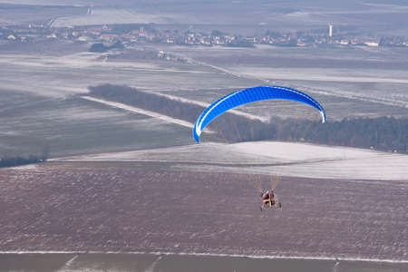 Aerial view of a paramotor ULM flying in winter in a snowy landscape in winter