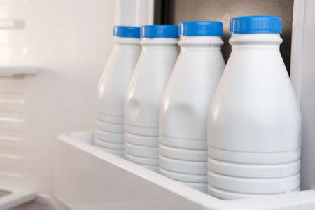 Group of plastic milk canisters stored and aligned in the fridge door. Calcium is good for your health
