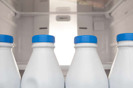Group of plastic milk bottle stored and lined up in refrigerator door