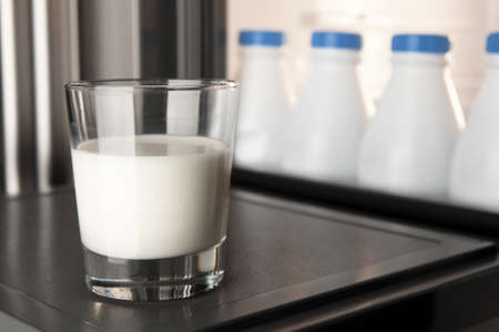 Close-up glass of milk on the fridge door with a group of plastic milk bottles stored and aligned in the background. Calcium is good for your health