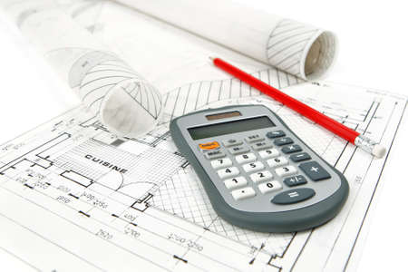 Close-up of calculator and pencil placed on home improvement plans with rolls of architectural drawings. Photo shoot isolated on white background. Banque d'images