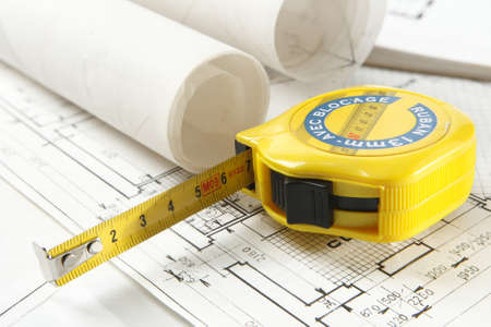 Interior design paper with construction plan in rolls and tape measure close-up Banque d'images