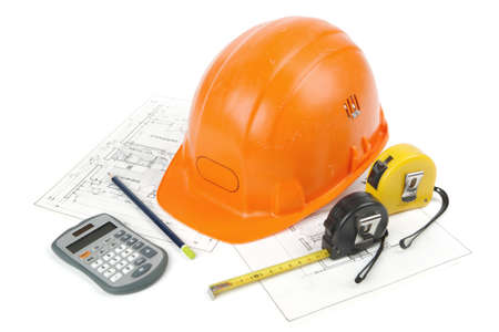 Concept of architecture and construction of the building with hard hat posed on paper plans, tape measures, a pencil and a calculator. photo shooting cut out and isolated on white background Banque d'images