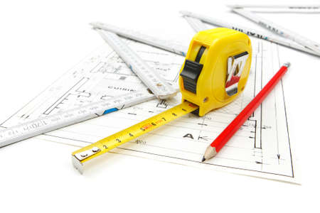 Work tools equipment arranged on house construction plans with tape measure, pencil and wooden ruler. Shooting studio photo isolated on white background.