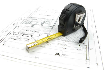 Measuring tape close up on a construction plan isolated on a white background