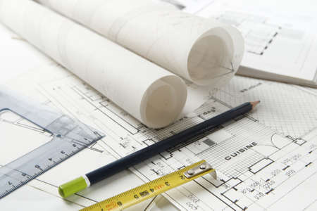Set of drawing work equipment laid on home and kitchen layout plans with rolls of architect drawings