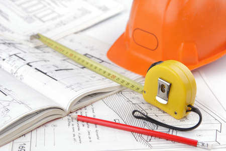 Construction safety helmet posed on architectural blueprints, tape measure in close-up, a pencil. Concept of architecture and construction of the building