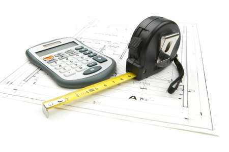 Tape measure with a calculator on the drawing plan of architectural and construction project, isolated on white background