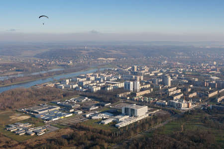 Aerial photography of a paramotor (motorized paraglider) flying over the large town of Mante-la-Jolie, in the Yvelines department (78200), Ile-de-France region, France - January 03, 2010