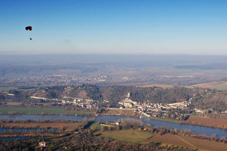 Aerial photography of a paramotor over flying La Roche-Guyon en Vexin and its castle, in Val-d'Oise department (95780), region Ile-de-France, France - January 03, 2010
