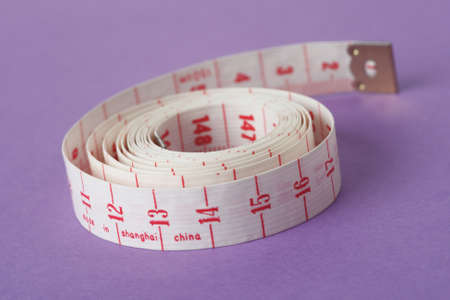 Measuring tape isolated on purple background and rolled up on itself Banque d'images