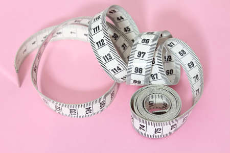 Unrolled spiral dressmaker's tape measure isolated on pink background