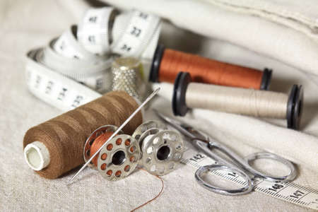 sewing tools with scissors, brown threads, needle and tape measure. Dressmakers accessories on beige fabrics