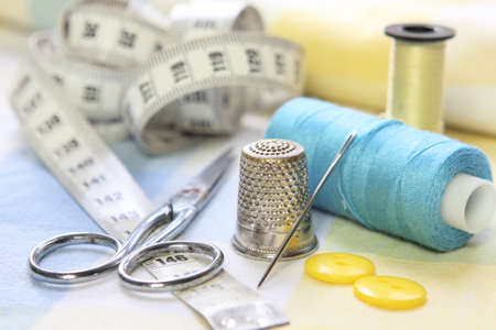 sewing tools with scissors, threads, needle and tape measure. Dressmakers accessories on blue and yellow fabrics Banque d'images