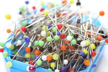 Multicolored dressmaker's needle push pins box on white background