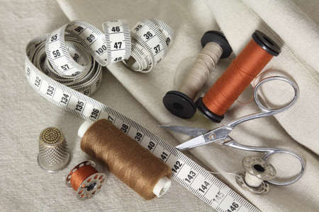 Set of sewing accessories: spools of brown thread, sepia and a needle, a pair of scissors and a tape measure. Tailor Accessories laid on beige fabrics Banque d'images
