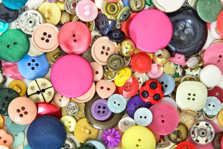Set of buttons and sewing accessories in very different colors, sizes and shapes. Predominantly pink and red and some yellow, blue and green buttons Banque d'images