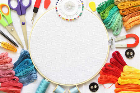 Embroidery hoop and multicolored accessories on white linen canvas with spools of thread, needle and scissors. Banque d'images