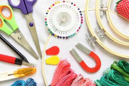embroidery hoop with sewing accessory, scissors, embroidery threads and needle on a white fabric canvas