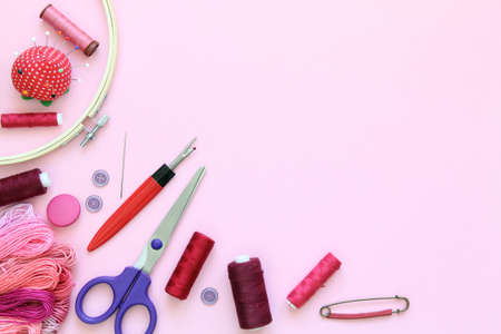 Composition with sewing accessories on a pink background with needles, a spool of thread, scissors and a measuring tape