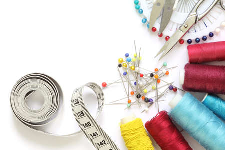 Sewing accessories template. Scissors, tape measure, spool of thread and needle on a white background. Banque d'images