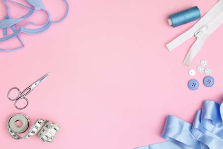 Sewing accessories on a pink background with needles, spool of thread, scissors and a tape measure