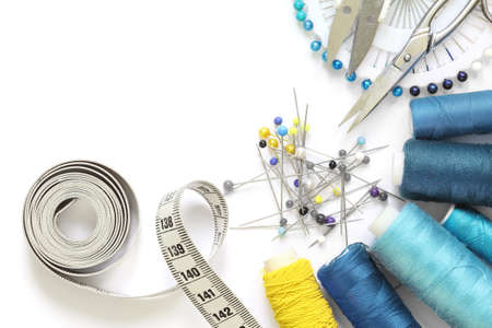 Blue and yellow sewing accessories template with scissors, tape measure, spool of thread and needle isolated a cut-out on white background.