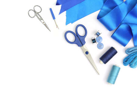 creative composition with blue sewing tools and accessories cut out and isolated in white frame with scissors, spools of threads and blue fabric ribbons Banque d'images