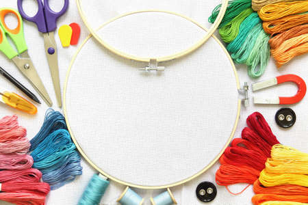 Multicolored embroidery accessories on white linen canvas. Embroidery hoop, spools of thread, needle and scissors.