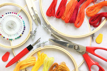 Embroidery accessories on white linen canvas. Embroidery hoop, threads, needle and scissors. color red and yellow