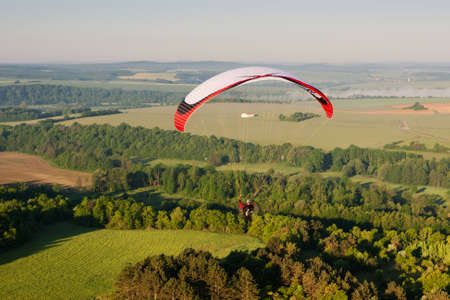 In morning, one paramotor flying over the fields in Yonne department, in Bourgogne-Franche-Comté region, France