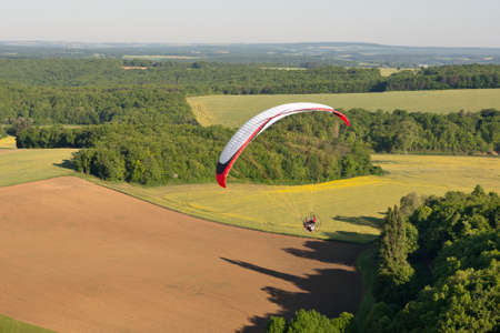The Yonne department seen from the sky by paramotor over fields, Bourgogne region, France