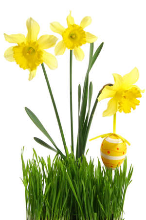 concept of spring season and french easter holidays: Green grass with bouquet of flowers and hanging Easter egg cut out and isolated on white background