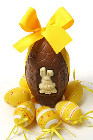 Easter party concept: Big chocolate egg with yellow ribbon, Easter bunny and decorative eggs, isolated on white background