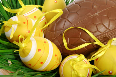 Yellow Easter eggs with ribbons on green grass, lying in a basket with a large chocolate egg