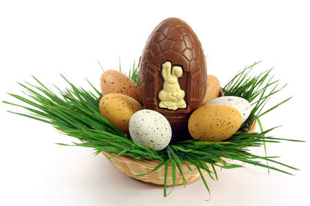 Big chocolate Easter eggs with small ones in a basket with green grass, cut out and isolated on white background Banque d'images