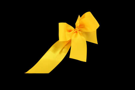 Decorative yellow ribbon and bow cut out and isolated on black background