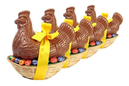 Set of chocolate Easter hen and chicken with yellow ribbon and bow, presented in a basket with decorative eggs, cut out and isolated on white background Banque d'images
