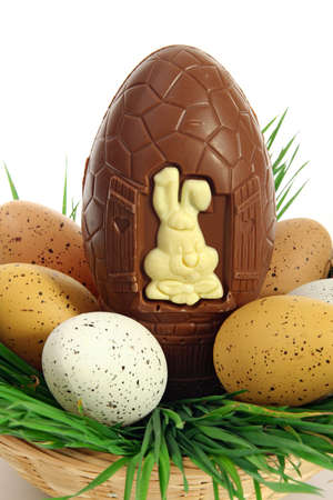 Traditional basket of Easter eggs on fresh grass with a large chocolate egg and a white rabbit