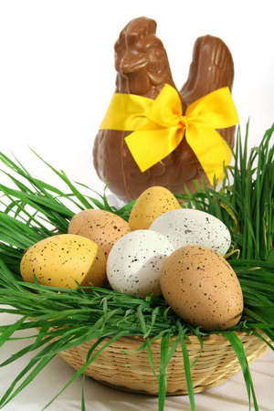 Easter concept: Basket of Easter eggs placed on fresh grass with a big chocolate hen with a yellow bow on a white background Banque d'images