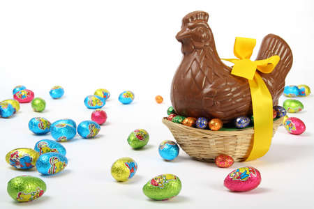 Chocolate Easter hen with yellow ribbon and bow, presented with colorful decorative eggs, isolated on white background