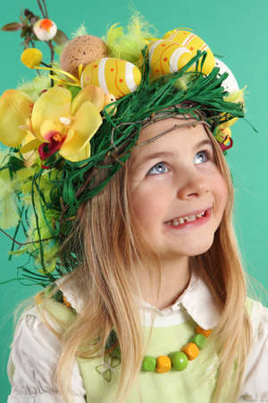 Happy Easter day. seven year old girl with festive Easter hairstyle made of yellow easter eggs, spring flowers and bird feathers. Smiling child looks up