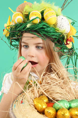 Cute little child wearing a fun hairstyle on Easter Day. Girl with basket of shiny eggs looks at an easter egg squinting