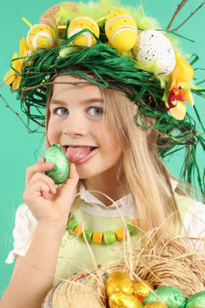 Portrait of a charming young girl wearing a festive hairstyle made with yellow Easter eggs, spring flowers and bird feathers. The child licks an easter egg that she is holding in her hand