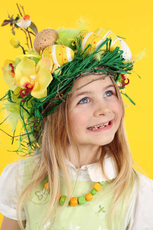 Happy girl having fun Easter egg hunt, wearing straw nest hairstyle made of spring flowers, Easter eggs and feathers. The child looks to the side smiling. Studio art portrait on yellow background.