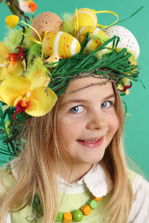 Portrait of a smiling blonde girl wearing hair dressing of yellow Easter eggs, spring flowers and bird feathers on a green background. The child looks at the camera