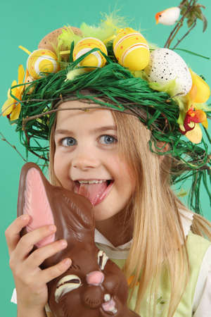 Easter concept. Child eating chocolate bunny. The young Girl wears a festive headdress made of yellow Easter eggs, spring flowers and bird feathers.