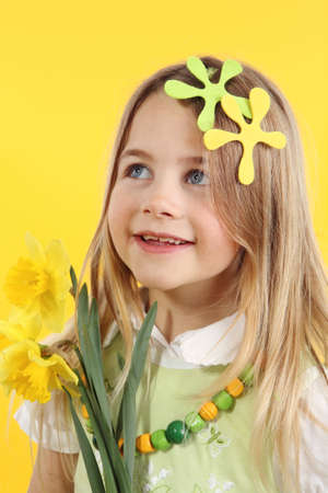 spring season concept: cute little girl with daffodil flowers for spring festival on yellow background. The child looks up to the side