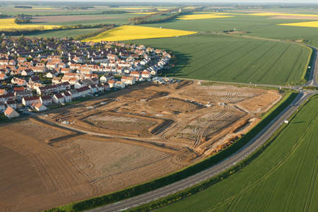 Aerial view of Ablis subdivision construction and rapeseed fields in spring, located in the south of the Yvelines department, ÃŽle-de-France region, France. Banque d'images